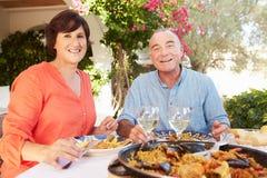 Pares latino-americanos maduros que apreciam a refeição exterior em casa Imagem de Stock