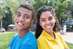 Pares latino-americanos novos com as camisas coloridas de volta à parte traseira Imagem de Stock Royalty Free