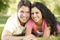 Pares latino-americanos novos românticos que relaxam no parque Fotografia de Stock Royalty Free