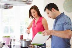 Pares latino-americanos que cozinham a refeição em casa fotos de stock