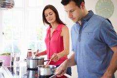 Pares latino-americanos que cozinham a refeição em casa imagens de stock royalty free