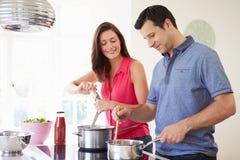 Pares latino-americanos que cozinham a refeição em casa imagem de stock