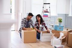 Pares latino-americanos que movem-se na casa nova e que desembalam caixas foto de stock royalty free