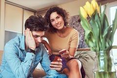 Pares latino-americanos que relaxam junto no sofá Usando smartphones ao descansar em casa imagem de stock