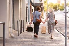 Pares lesbianos felices que caminan en los panieres que llevan de la ciudad Fotos de archivo libres de regalías