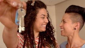 Pares lesbianos felices que llevan a cabo llaves almacen de video
