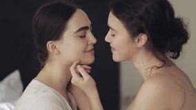 Pares lesbianos felices que se abrazan y que sonr?en en casa cara a cara en la c?mara lenta almacen de metraje de vídeo