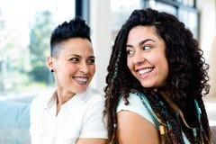 Pares lesbianos felices que se sientan de nuevo a la parte posterior Fotos de archivo libres de regalías