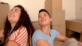 Pares lesbianos felices que se sientan en piso y que miran la nueva casa metrajes