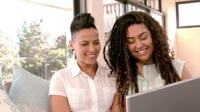 Pares lesbianos felices usando el ordenador portátil junto en el sofá almacen de metraje de vídeo