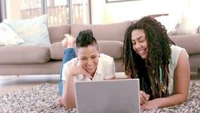 Pares lesbianos felices usando el ordenador portátil que pone en la alfombra metrajes