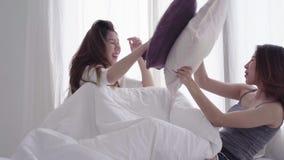 Pares lesbianos jovenes asiáticos que juegan el uno al otro con el momento del amor en la cama en el dormitorio rodeado con luz d almacen de video