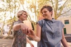 Pares lesbianos jovenes cariñosos que sonríen y que bailan en la ciudad Imagen de archivo libre de regalías