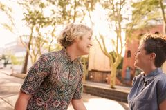 Pares lesbianos jovenes despreocupados que ríen y que bailan en la ciudad Imagenes de archivo