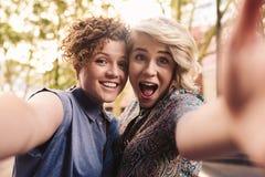 Pares lesbianos jovenes despreocupados que toman selfies en la ciudad Fotos de archivo libres de regalías
