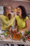 Pares lesbianos jovenes en cocina Foto de archivo libre de regalías