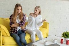 Pares lesbianos jovenes en pelea, ropa casual que lleva fotografía de archivo libre de regalías