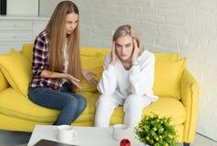 Pares lesbianos jovenes en pelea, ropa casual que lleva, sent?ndose en el sof? amarillo en casa imagen de archivo