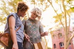Pares lesbianos jovenes hacia fuera que hacen compras junto en la ciudad Fotografía de archivo