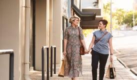 Pares lesbianos jovenes que caminan con los panieres en la ciudad Imagenes de archivo