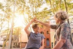 Pares lesbianos jovenes que llevan a cabo las manos y que bailan en la ciudad Fotografía de archivo libre de regalías