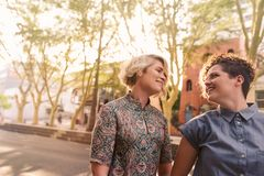 Pares lesbianos jovenes sonrientes que caminan junto en una calle de la ciudad Fotografía de archivo libre de regalías