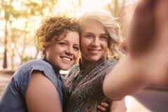Pares lesbianos jovenes sonrientes que toman selfies juntos en la ciudad Foto de archivo libre de regalías