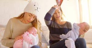 Pares lesbianos que confortan a su bebé en la sala de estar 4k almacen de video