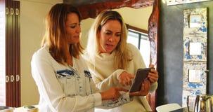 Pares lesbianos que discuten sobre la tableta digital en la cocina 4k metrajes