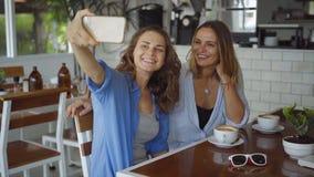 Pares lesbianos que fechan en café Dos mujeres hermosas que toman la foto del selfie en la cámara lenta metrajes