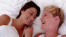 Pares lesbianos que ríen en cama almacen de metraje de vídeo