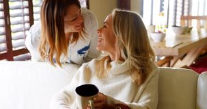 Pares lesbianos que se besan mientras que usa el telecontrol de la TV en el sofá 4k almacen de video