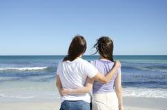 Pares lesbianos que se unen en el océano Imagen de archivo libre de regalías