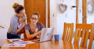 Pares lesbianos que trabajan en el ordenador portátil en la sala de estar 4k almacen de metraje de vídeo