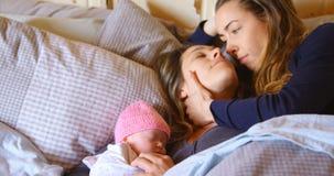 Pares lesbianos romancing mientras que se relaja con su bebé en el dormitorio 4k almacen de metraje de vídeo