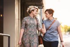Pares lesbianos sonrientes que caminan con los panieres en la ciudad Imagenes de archivo