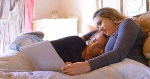 Pares lesbianos usando el ordenador portátil en el dormitorio 4k metrajes