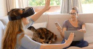 Pares lesbianos usando las auriculares y el ordenador portátil de la realidad virtual en la sala de estar 4k metrajes