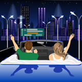 Pares libres felices que conducen en coche del cabriolé en animar de la ciudad de la noche alegre con los brazos aumentados Fotos de archivo libres de regalías