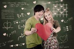 Pares lindos con la tarjeta del corazón de la tarjeta del día de San Valentín Imagenes de archivo