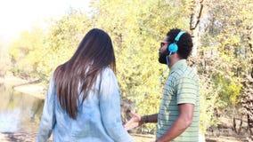 Pares lindos con los auriculares que escuchan la música y que bailan por el lago almacen de video