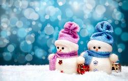 Pares lindos de los muñecos de nieve con el fondo azul del invierno Imagen de archivo libre de regalías