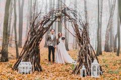Pares lindos do casamento sob o arco côr de avelã misterioso decorado com as decorações em madeiras do outono Fotos de Stock