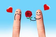 Pares lindos en amor con el smiley, dando una rosa con el cielo azul. Imagen de archivo