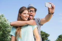 Pares lindos en el parque que toma el selfie Foto de archivo libre de regalías