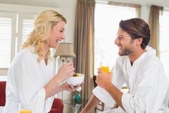 Pares lindos en las albornoces que desayunan junto Imagenes de archivo