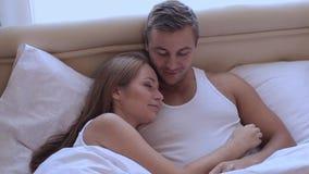 Pares lindos hermosos jovenes que mienten en cama por la mañana, el abarcamiento y la sonrisa almacen de metraje de vídeo