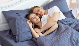 Pares lindos jovenes que duermen junto en cama en nuevo hogar foto de archivo