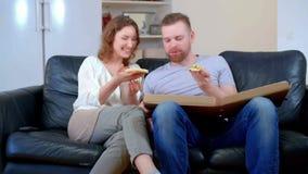 Pares lindos que comen la pizza y que ven la TV en la sala de estar La pizza era terrible almacen de metraje de vídeo