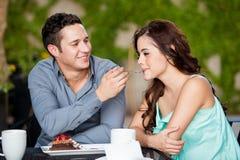 Pares lindos que comparten la torta en un café Imagen de archivo libre de regalías